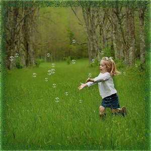 Счастливая девочка бежит ловит пузырив поле